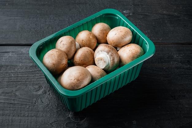 플라스틱 팩에 검은 나무 테이블 배경에 원시 버섯 champignons 세트