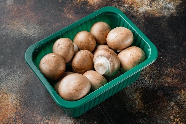 플라스틱 팩에 있는 오래된 어두운 소박한 배경에 생 버섯 샴피뇽 세트