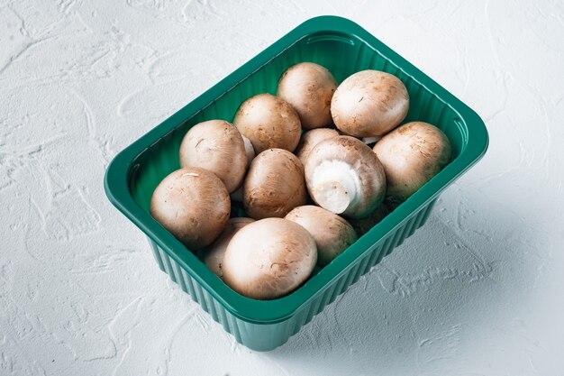 플라스틱 팩에 흰색 배경에 원시 버섯 champignons 세트