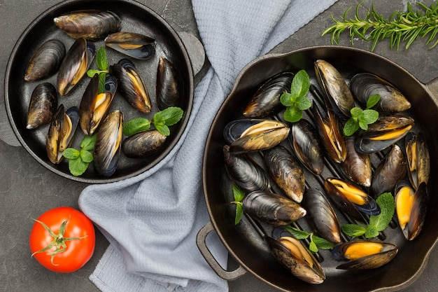 Raw mussels in shells with mint in frying pan. gray napkin between two pans. flat lay