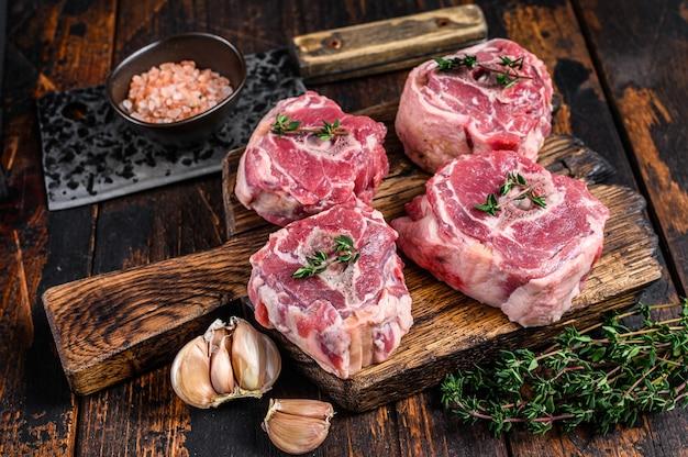 Сырое мясо ягненка из баранины на доске мясника с тесаком.