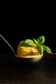 Raw nest noodles with basil leaves in a ladle on a dark background