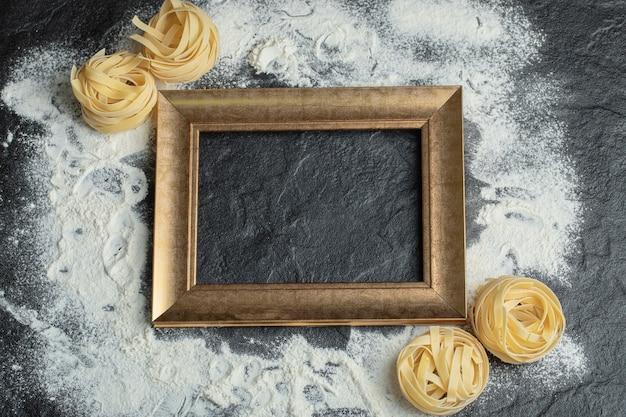 Сырые макаронные изделия гнезда с мукой и рамкой на черном.