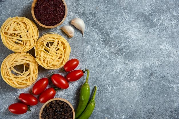 Сырые макаронные изделия гнезда со специями и овощами.