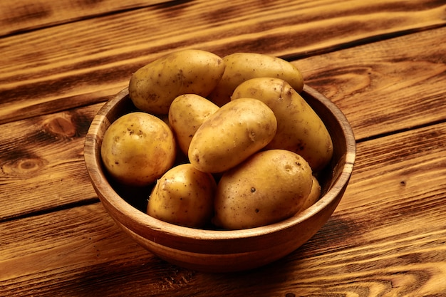 Raw new potatoes in a wooden dish on wooden background