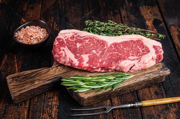 나무 보드에 원시 뉴욕 스트립 쇠고기 스테이크 또는 striploin