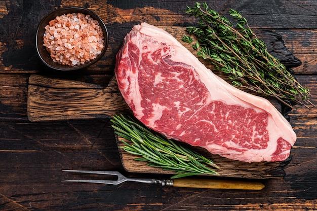 Сырой нью-йоркский стейк из говядины или стриплойн на деревянной доске