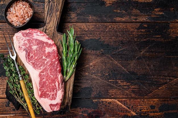 Raw new york strip beef steak or striploin on a wooden board