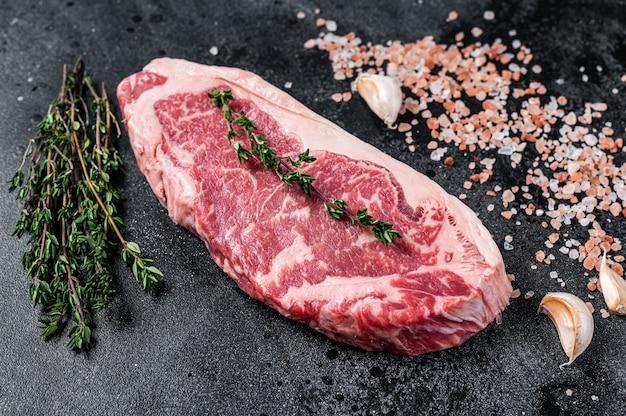 肉屋のテーブルに塩とタイムを添えた生のニューヨークストリップステーキ。黒の背景。上面図。