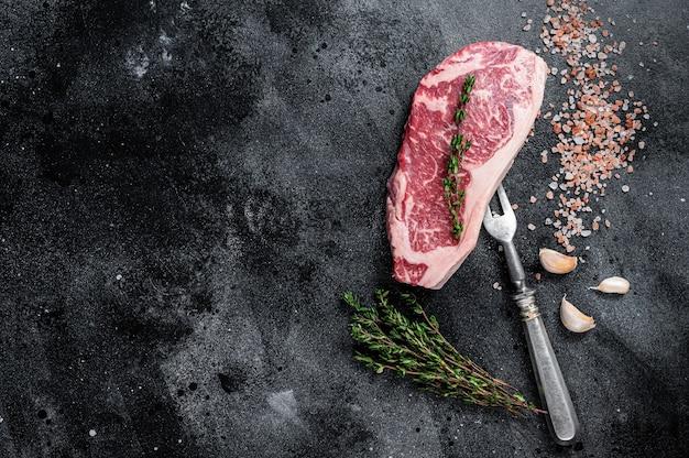 肉屋のテーブルに塩とタイムを添えた生のニューヨークストリップステーキ