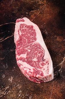 肉屋のテーブルで生のニューヨークストリップステーキまたはサーロイン。暗い背景。上面図。