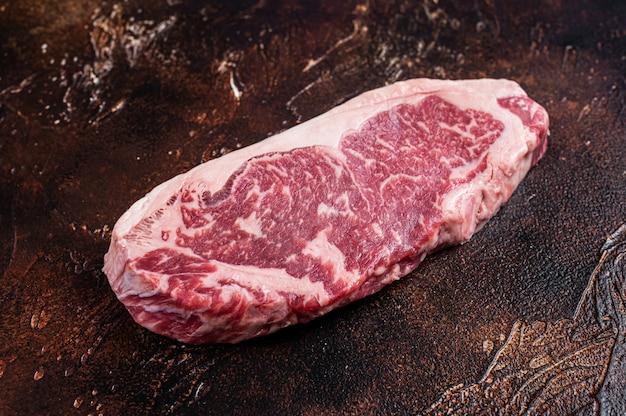 肉屋のテーブルで生のニューヨークストリップステーキまたはサーロイン