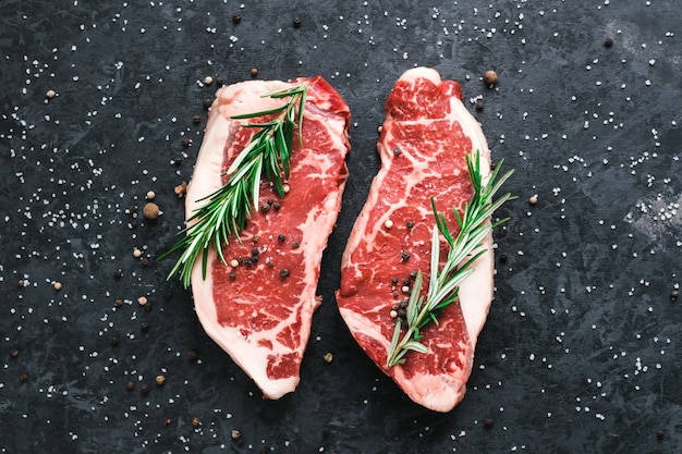 Raw new york striploin beef steak isolated on black with sea salt and rosemary and spices.