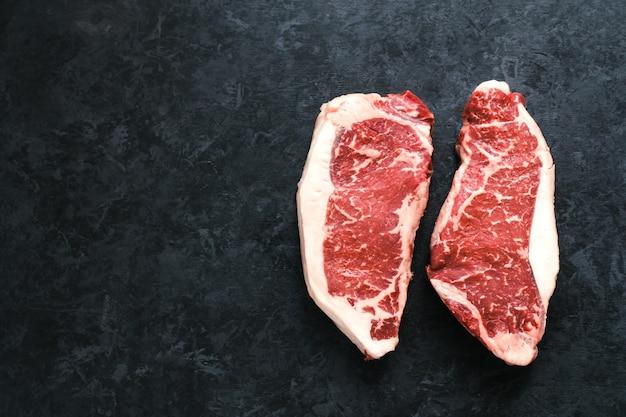 Сырой стейк из говядины нью-йорк стриплойн, изолированные на черном