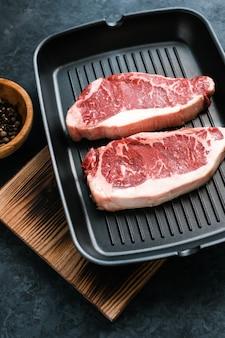 Сырой стейк из говядины нью-йорк стриплойн на черной сковороде с перцем чили