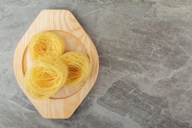 Nidi di pasta cruda su piatto di legno