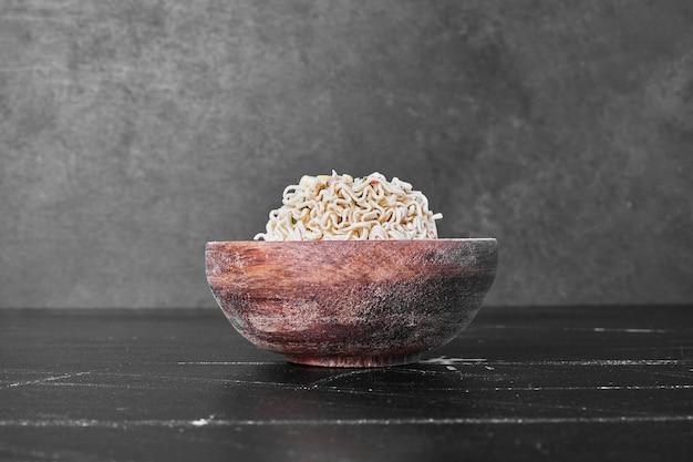 Сырая лапша или спагетти в деревянной миске