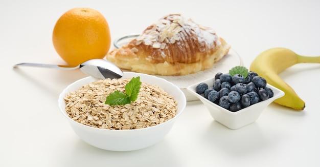 흰색 세라믹 접시, 블루베리, 오렌지, 바나나, 흰색 테이블에 생 오트밀, 아침 식사