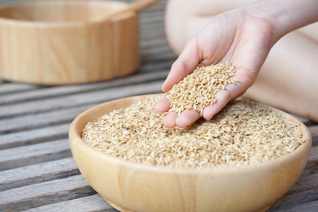 下に一杯のオーツ麦を入れた女性の手からの生のオーツ麦。健康的なライフスタイルの概念。