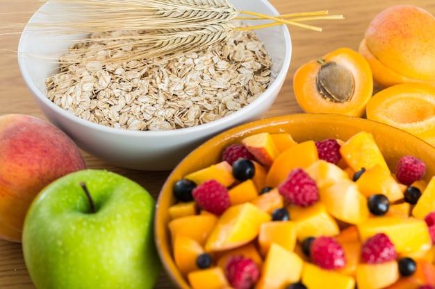 ボウルとフルーツサラダの生のオーツ麦、木製のテーブルの上のリンゴ Premium写真
