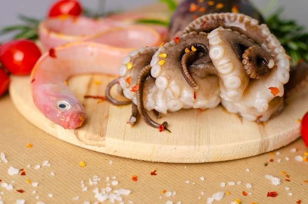 Raw octopus and fish ready for cooking on a wooden cutting board with copy space