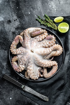 Сырой осьминог в тарелку с приготовления ингредиентов. черная поверхность. вид сверху