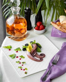 Raw octopus meat with herbs and lemon.