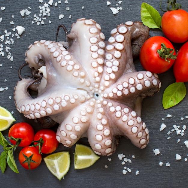 Сырой осьминог с лаймом, помидорами и базиликом на темной поверхности