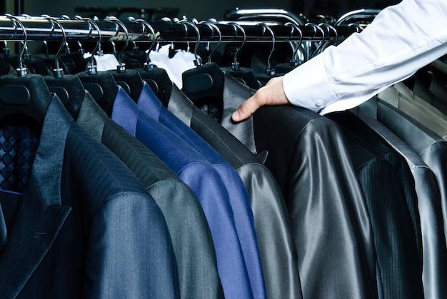 ぶら下がっているさまざまな色の男のジャケットの生