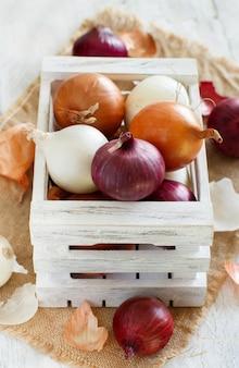 Сырой лук в коробке на деревянном столе