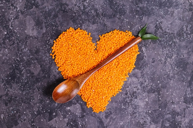 Raw orange lentils for proper nutrition and health in the form of a heart with a wooden spoon and leaves on a gray background