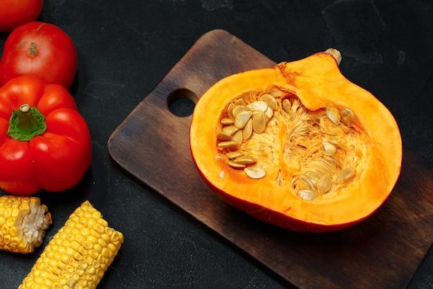 Сырая оранжевая тыква и деревянная разделочная доска