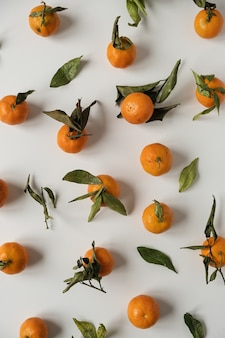 Raw oranges, mandarins fruits with green leaves pattern on white