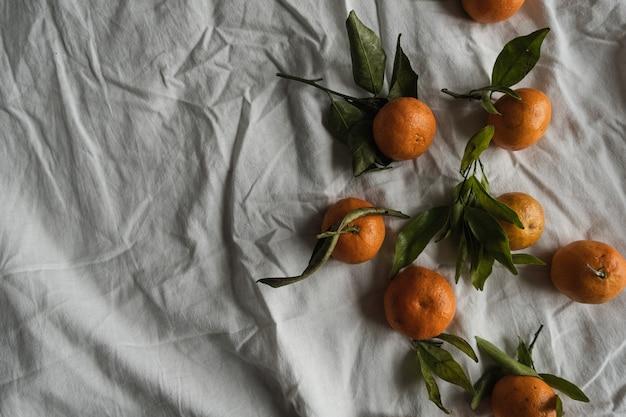 生オレンジ、しわくちゃの布にみかん。新鮮で健康的な果物