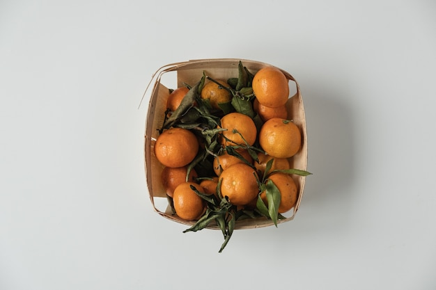 Raw oranges, tangerines with green leaves in basket on white