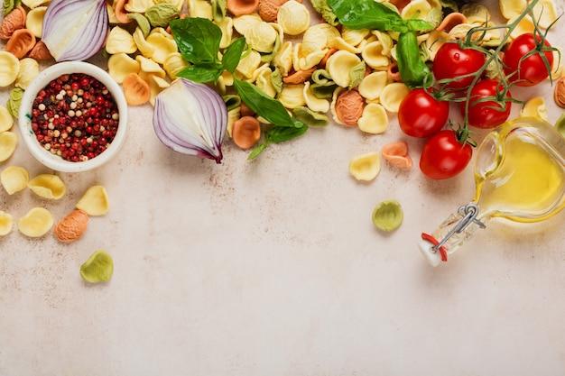 Сырой орекьетте с сыром пармезан и помидорами, базиликом, чесноком и маслом на светлой стене с перцем на светло-коричневой стене. традиционные ингредиенты для приготовления итальянской пасты. вид сверху.