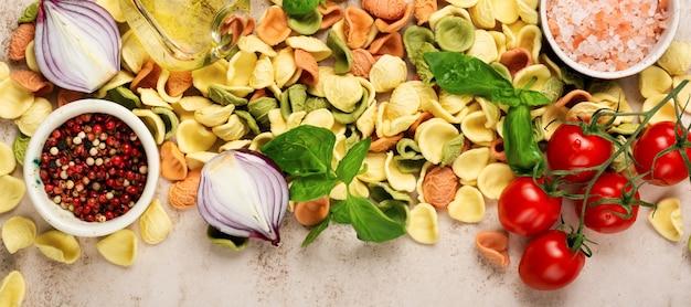 Сырой орекьетте с сыром пармезан и помидорами, базиликом с чесноком и маслом на светлой стене. традиционные ингредиенты для приготовления итальянской пасты. баннер. вид сверху.