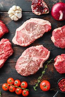 Raw organic alternative beef steakes top blade cut with seasonings and herbs on old rustic dark wooden table, top view.