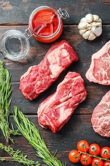 원시 유기농 대체 쇠고기 스테이크 척 롤은 오래 된 소박한 어두운 나무 테이블, 평면도에 조미료와 허브로 잘라.