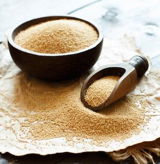 木製のテーブルのボウルに生の有機アマランサスの穀物