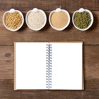 Raw organic amaranth and quinoa grains, wheat and mung beans in bowls on wooden table top view with notebook copy space