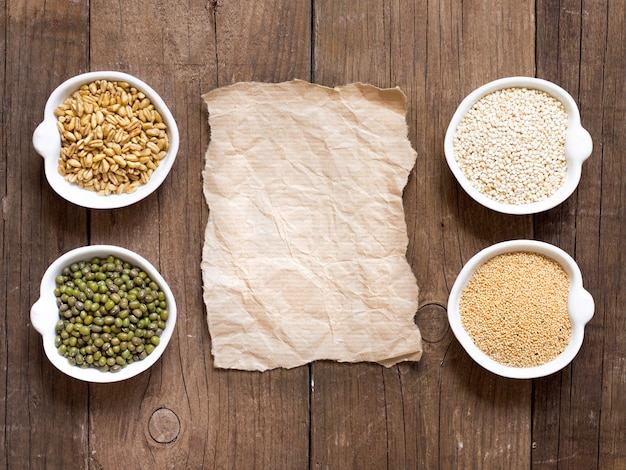Raw organic amaranth and quinoa grains, wheat and mung beans in bowls on wooden table top view with paper copy space