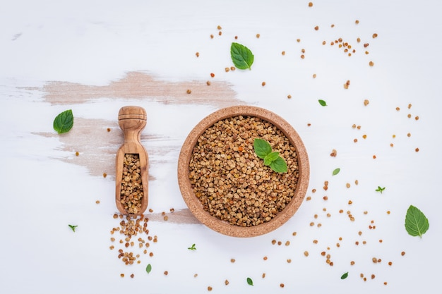 Raw organic bee pollen with peppermint and thyme on white background .