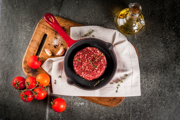 Raw organic beef meat burgers cutlets  with spices, thyme, tomatoes, olive oil in frying pan on black ,  copyspace top view