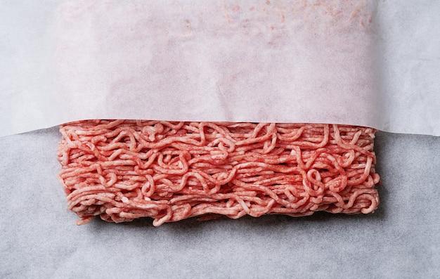 흰 종이 포장에 원시 유기농 쇠고기 다진 고기. 평면도. 플랫 레이.