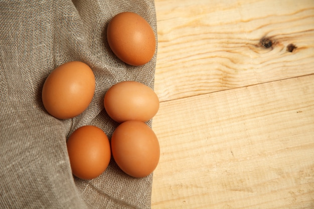 Raw organic brown eggs over linen napkin and rustic wooden background