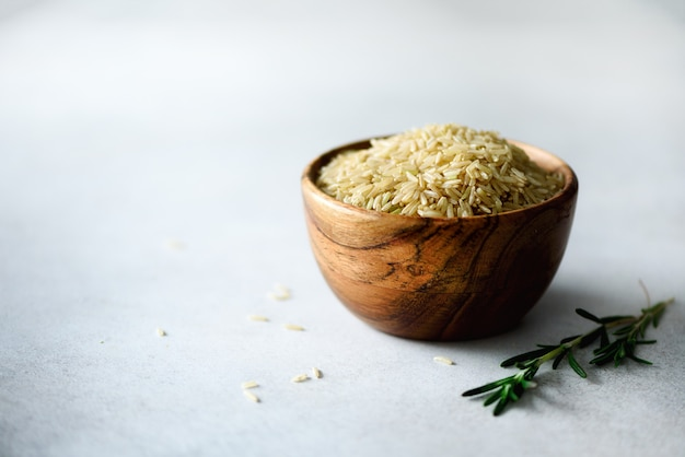 Raw organic brown rice in wooden bowl and rosemary on light concrete. food ingredients. copy space