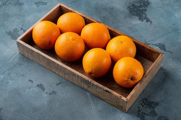 生の有機カラカラネーブルオレンジセット、木製の箱、灰色の石のテーブル