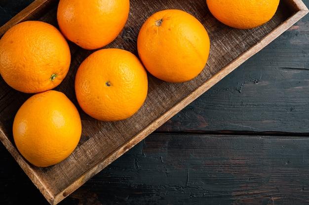 生のオーガニックカラカラネーブルオレンジセット、木製の箱、古い暗い木製のテーブル、上面図フラットレイ
