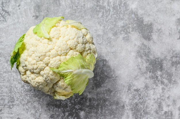 Raw organic cauliflower with leaves. top view. copy space